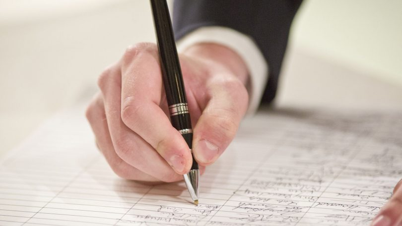 A photograph showing a hand holding a pen and signing a document