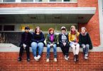 Antioch College students sit together on a red brick wall