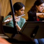 Austin College students plays flute in the orchestra