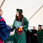 Evergreen's President congratulates a graduate holding her degree