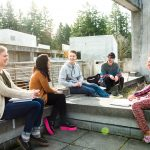 Students meet in a group outside to discuss class readings