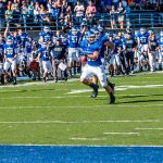 A Hillsdale College football player runs with the ball