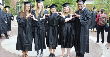 Graduates make heart shapes with their hands