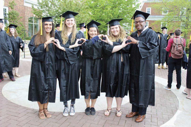 """e6e87c69101 Graduates make heart shapes with their hands. """""""