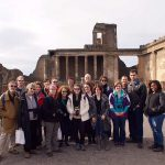 Emory & Henry College students and professors stand in front of an ancient building