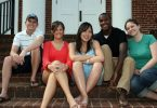Five Lynchburg College students sit on the campus steps together