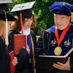 Lynchburg College graduates look over their diplomas with professors