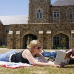 Rhodes College students read books on the campus lawn