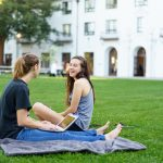 Two students sit on the lawn in front of a college building