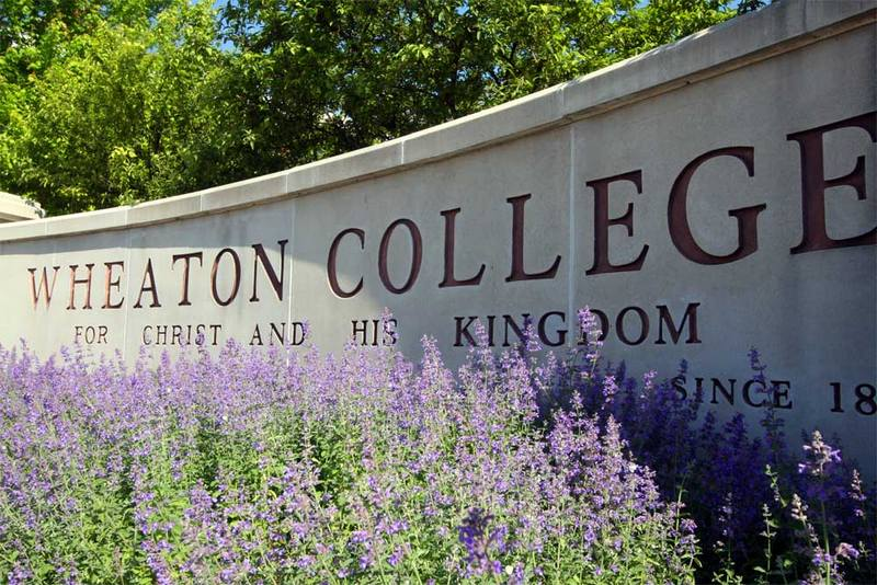 Flowers bloom in front of the Wheaton College campus sign