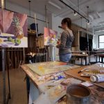 A Wheaton College student paints in an art studio
