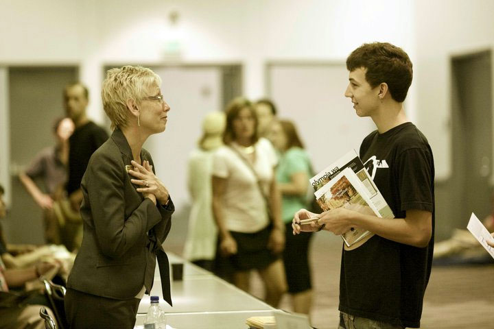 College counselor speaks with a student at a college fair