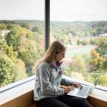 Student studies in view of Denison's football stadium and Biological Reserve