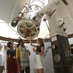 Agnes Scott students examine the Lewis A. Beck Telescope in the Bradley Observatory.