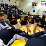 Centre College varsity basketball players huddle before a game