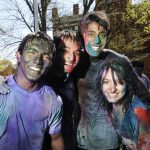 Smiling students covered in colored powder during Holi, a festival of colors