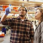 A Clark student and a professor look at a biological sample