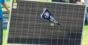 Hampshire students carry a solar array on campus