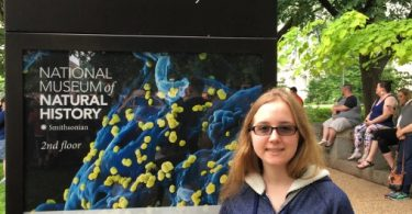 St. Olaf student stands in front of the Smithsonian Natural History Museum sign