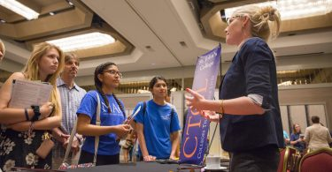 A college counselor speaks with students at a CTCL college fair.