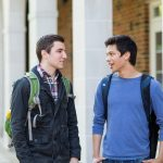 Two male students talking in front of Dewing Hall at Kalamazoo College.