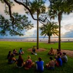 First-year students gather in a circle on the New College Bayfront during orientation.