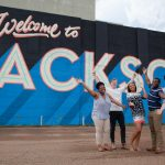 Millsaps students in front of a sign that reads Welcome to Jackson