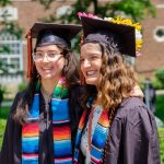 Two graduating students in their cap and gown at a Kalamazoo College commencement