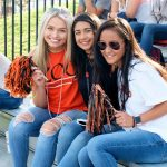 Three students cheer on the Kalamazoo College football team at Homecoming