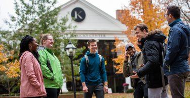 Six students gather near the Hicks Student Center at Kalamazoo College.