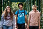 Three Guilford College students walk by the Orangerie at Binford Hall.