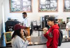 Two Guilford College students enjoy iced drinks at Rachel's Rose Cottage, the on-campus coffee shop.
