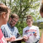 students work with a professor outdoors