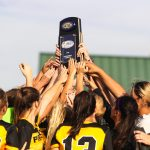 women's soccer players hold up a trophy together