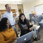 Goucher students and professors work in a lab together.