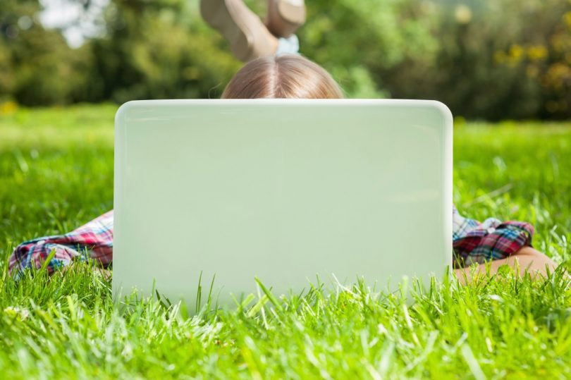 Computer and fresh air. Woman hiding face behind laptop monitor while lying on the grass in park