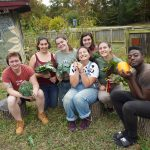 Seven Goucher students are holding fresh vegetables from a garden