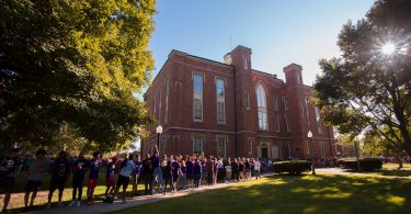 students walk across Knox College campus during the Pumphandle event